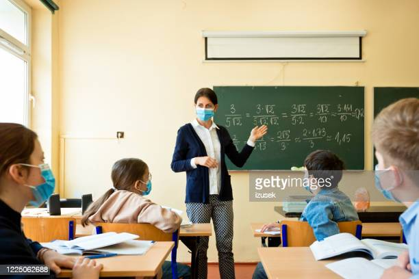 covid-19. a teacher teaches mathematics - protective face mask stock pictures, royalty-free photos & images