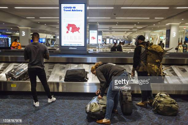 Covid-19 advisory is displayed on a screen as travelers collect luggage in the baggage claim area of Terminal B at LaGuardia Airport in New York,...