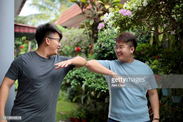 covid-19 alternative to handshakes - elbow bump stock pictures, royalty-free photos & images