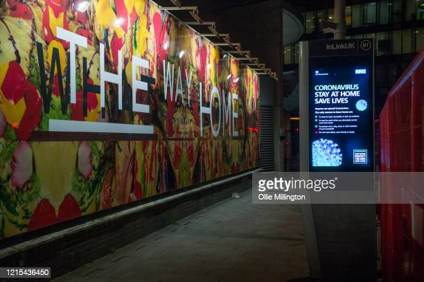 Covid-19 awareness poster saying stay at home seen next to a large advert for new homes on March 28, 2020 in London, England. British Prime Minister,...