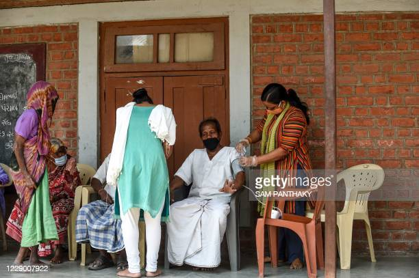 Covid-19 Awareness Project' volunteer checks the blood pressure of a patient as part of a general health checkup for all inmates at the Gandhi...