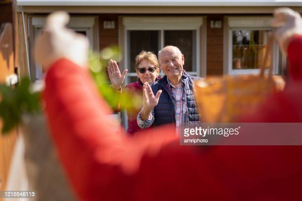 covid-19 food delivery, happy senior couple waving in front of their house - epidemiology stock pictures, royalty-free photos & images