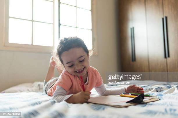 covid-19: girl drawing in bed during quarantine - epidemiology stock pictures, royalty-free photos & images