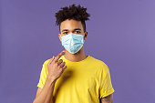 Covid19, healthcare and medicine concept. Young hispanic guy with afro haircut, wear and point at face mask, social-distancing during pandemic, explain friends how to prevent catching disease