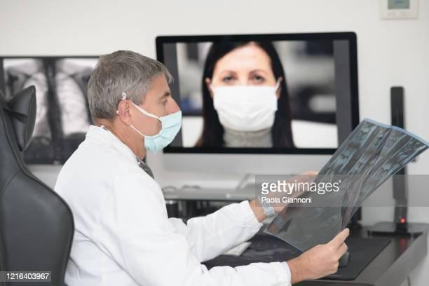コヴィッド-19.病院。居心地の良い19に苦しんでいる患者とラップトップ上の電話会議で外科マスクを持つ筆記医。医師はx線を調べています - x ray image ストックフォトと画像