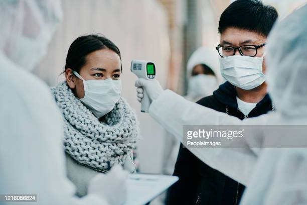covid-19 is keeping the healthcare industry very busy - infrared thermometer stock pictures, royalty-free photos & images