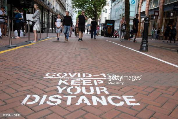 Covid-19 keep your distance signs painted on the pavement as the Coronavirus lockdown measures ease, the city centre starts to fill with people as...