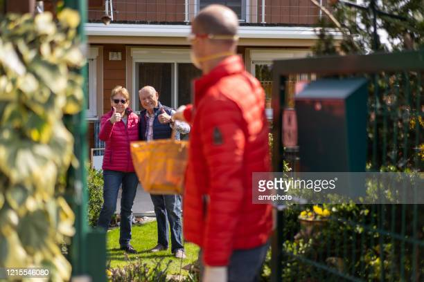 covid-19 man delivering food for smiling senior couple in garden - stay at home order stock pictures, royalty-free photos & images
