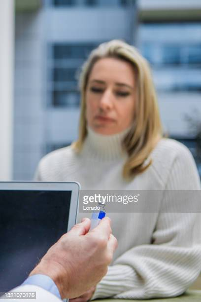 a covid-19 medical consultation between doctor and patient - between stock pictures, royalty-free photos & images