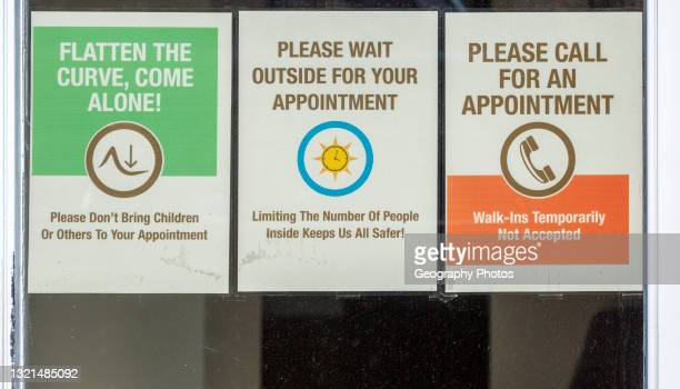 Covid-19 notices about precautions to be taken on glass window of hairdresser shop, UK.