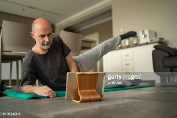 covid-19 allenamento di fitness sportivo online a casa - solo un uomo maturo foto e immagini stock