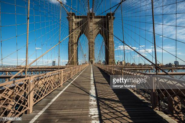 covid-19 pandemic - empty city - brooklyn bridge - brooklyn skyline, nyc - empty streets stock pictures, royalty-free photos & images