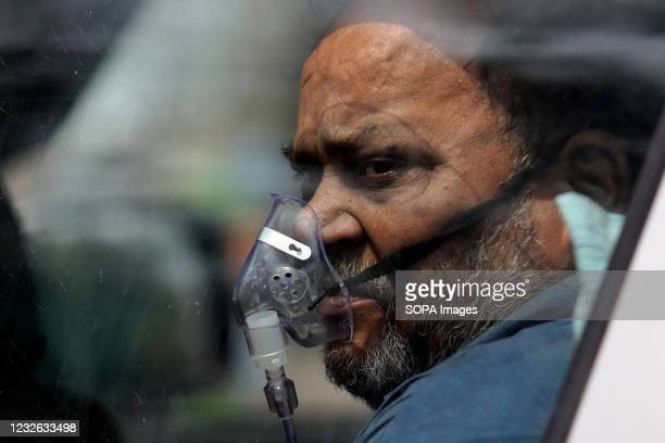 Covid-19 patient who is suffering from breathing difficulty breaths with the help of oxygen mask in his car outside the Guru Tech Bahuder Hospital in...
