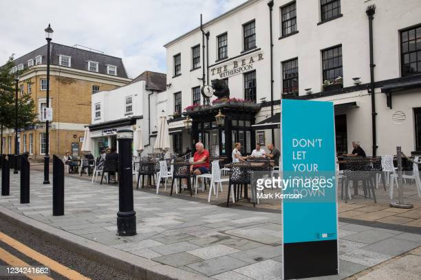 Covid-19 public health information sign is pictured in front of local residents enjoying refreshments outside a JD Wetherspoon public house on 27th...