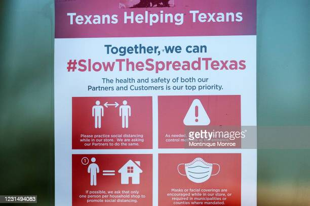 Covid-19 restriction signs hang outside of H-E-B supermarket on March 3, 2021 in Austin, Texas. The popular Texas supermarket chain will not require...