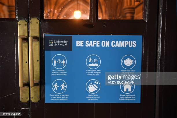 Covid-19 safety sign is attached to a door at the Glasgow university complex, Glasgow, Scotland on September 24, 2020. - An outbreak of Covid-19 has...