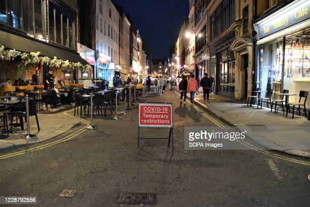 Covid-19 sign marks the traffic restrictions on Frith Street in Soho. Sections of Soho have been blocked for traffic to allow temporary outdoor...