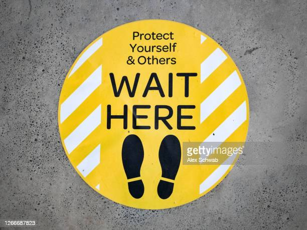"""covid-19 signage on pavement, yellow sticker with """"wait here"""" - pre labeled stock pictures, royalty-free photos & images"""