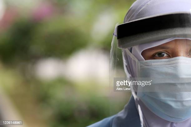 covid-19: smiling behind the mask - face shield stock pictures, royalty-free photos & images