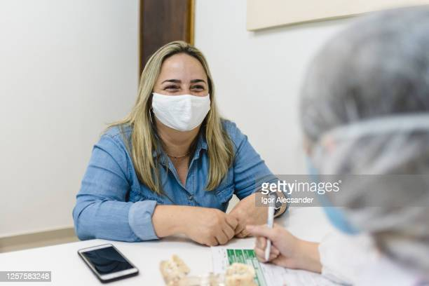covid19: smiling woman during medical consultation - outpatient care stock pictures, royalty-free photos & images