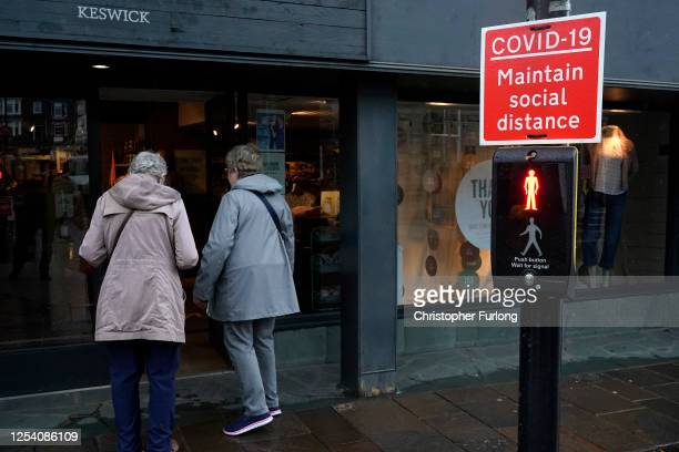 Covid-19 social distancing sign is placed on a traffic light in Keswick town centre on July 03, 2020 Keswick, United Kingdom. Despite a gloomy...