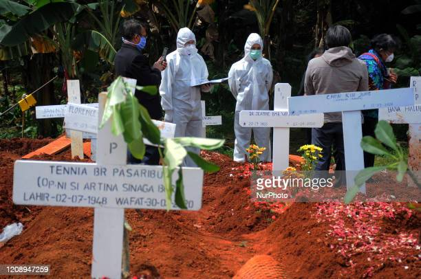 Covid19 Special Funeral Officers lift the coffin of a dead victim of the Covid19 virus at the Pondok Rangon Cemetery East Jakarta on April2020...