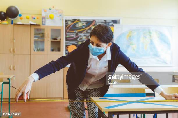 covid-19 the teacher marks empty places in the classroom - izusek stock pictures, royalty-free photos & images