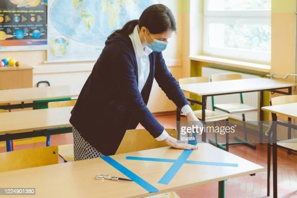 covid-19 l'enseignant marque vide assis dans la salle de classe - enseignante photos et images de collection
