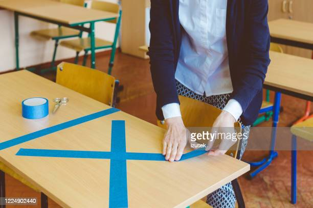 covid-19 the teacher marks empty sits in the classroom - izusek stock pictures, royalty-free photos & images
