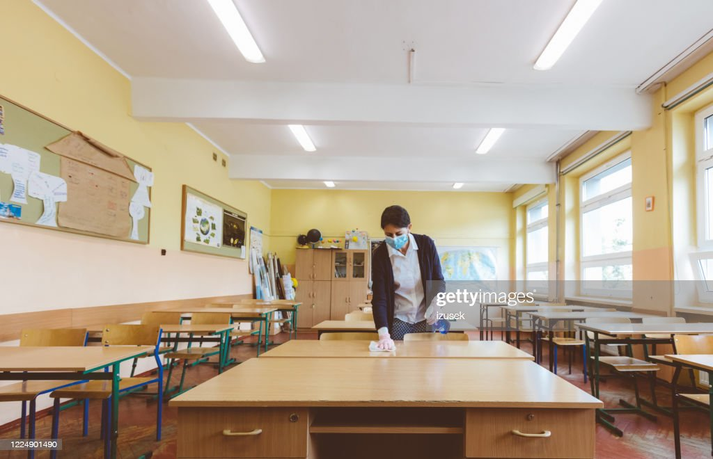 Covid-19 The teacher wipes down school tables at  classroom : Stock Photo