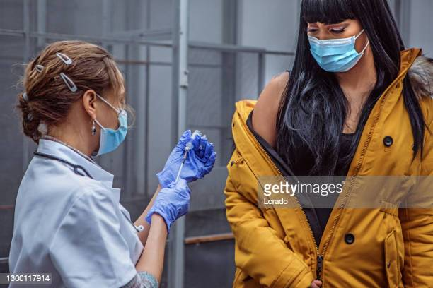 covid-19 vaccinations in an indoor medical setting - vaccination center stock pictures, royalty-free photos & images