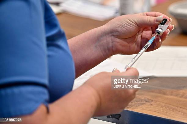 Covid-19 vaccine is prepared at a vaccination centre in Barrhead, south of Glasgow on August 9 where First Minister Nicola Sturgeon met staff and...