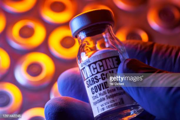 covid-19 vaccine - medical injection vials: hand holding, close-up and colorful - covid 19 vaccine stock pictures, royalty-free photos & images