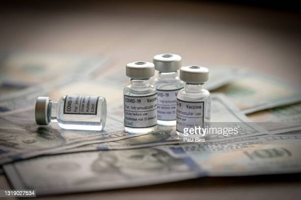 covid-19 vaccine on a stack of us  dollar and euro banknotes bills - centers for disease control and prevention stock pictures, royalty-free photos & images