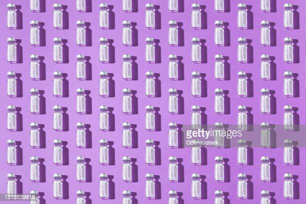 covid-19 vaccine vial pattern on purple background - logo stock pictures, royalty-free photos & images