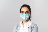 Covid19, virus, health and medicine concept. Portrait of young asian woman wearing medical face mask to prevent getting infected by coronaviruts, staying safe home during quarantine, pandemia