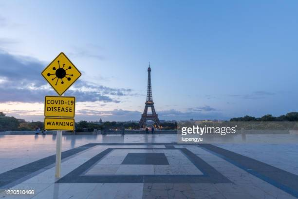 covid-19 warning sign with eiffel tower,paris - france stock-fotos und bilder