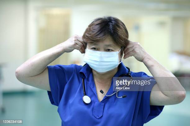 covid-19: wearing surgical mask in hospital - frontline worker stock pictures, royalty-free photos & images