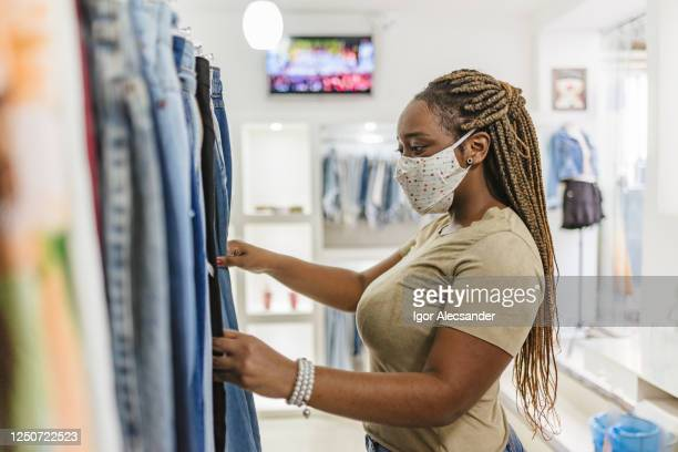covid-19: woman customer choosing clothes at the mall store - merchandise stock pictures, royalty-free photos & images