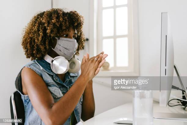 covid-19: woman in the office rubbing her hands with alcohol gel - rubbing alcohol stock pictures, royalty-free photos & images