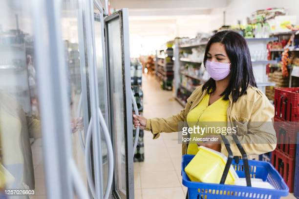 covid-19: woman opening a refrigerator in the supermarket - pardo brazilian stock pictures, royalty-free photos & images
