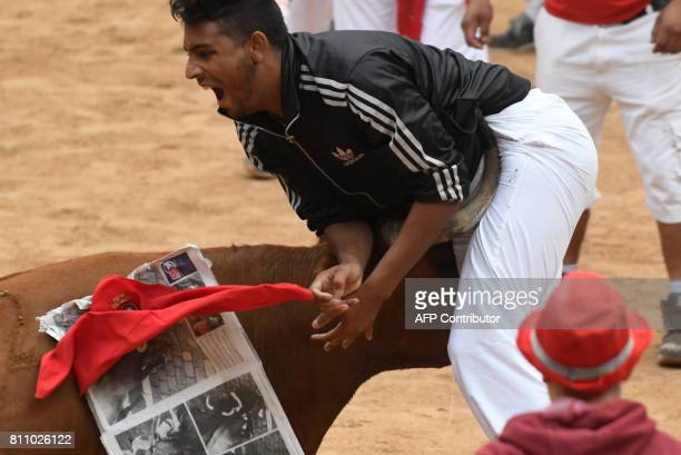 A cow charges a participant at the Pamplona's bullring during a show after the third 'encierro' of the San Fermin Festival in Pamplona northern Spain...