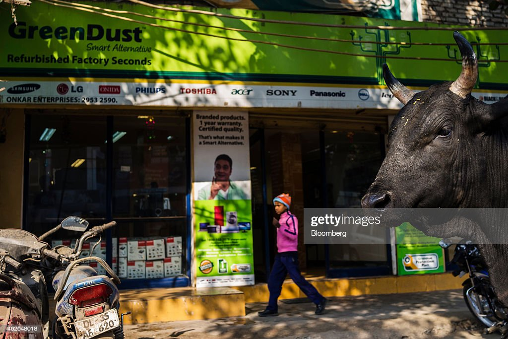 A cow stands outside a store of GreenDust, a unit of Reverse Logistics Co., in the Neb Serai area of New Delhi, India, on Friday, Jan. 16, 2015. Reverse Logistics, an Indian retailer of refurbished goods, is a factory outlet store in India selling goods through its GreenDust brand franchise stores and website. Photographer: Prashanth Vishwanathan/Bloomberg via Getty Images