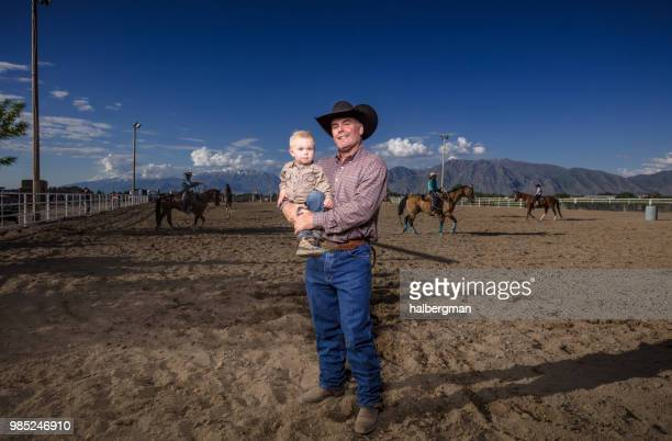 Cowbay Dad and Baby Son in Rodeo Arena
