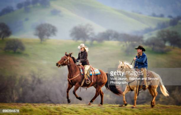 cowboy and cowgirl on horseback with panned motion - 乗馬ズボン ストックフォトと画像