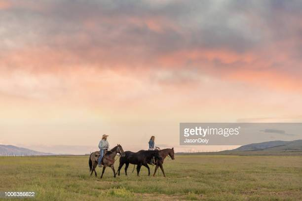 cowboy and cowgirl ride into the sunset - wild west stock pictures, royalty-free photos & images