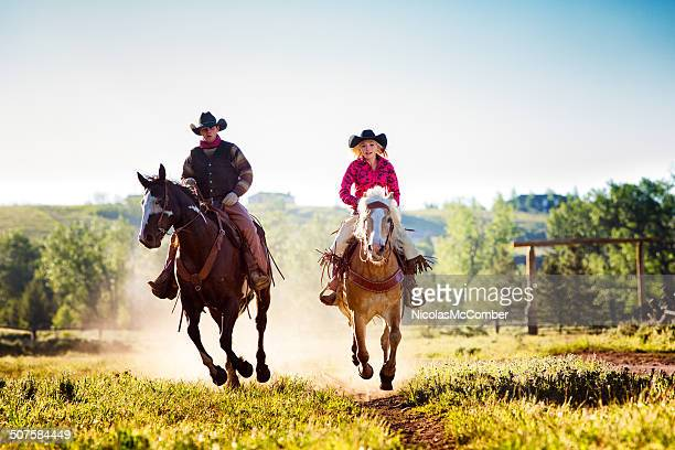 Cowboy and cowgirl riding on ranch