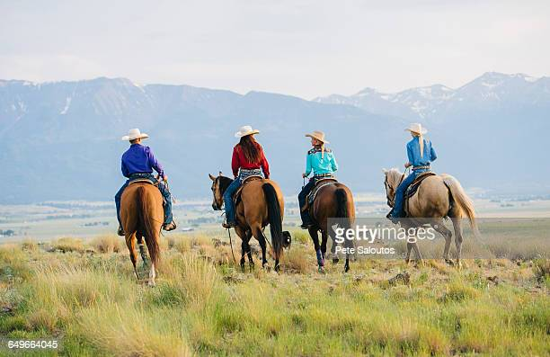cowboy and cowgirls riding horseback on ranch - cowgirl photos et images de collection