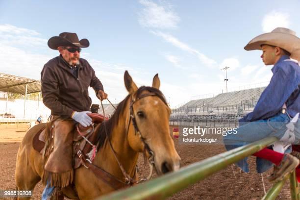 cowboy and grandson in rodeo paddock arena at nephi of salt lake city slc utah usa - spanish fork utah stock pictures, royalty-free photos & images