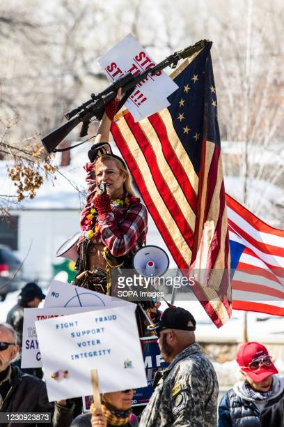 Cowboy Barbie holds a rifle in the air during the demonstration. Protesters gathered at the state's legislative building to protest various causes...